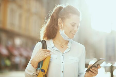 Life during coronavirus pandemic. smiling modern woman in blue blouse with medical mask and handbag using smartphone app outdoors in the city. Stock fotó