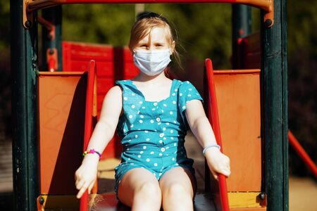 Life during coronavirus pandemic. modern girl in blue overall with medical mask playing on the playground outdoors in the city.
