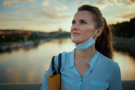 Life during covid-19 pandemic. happy young female in blue blouse with medical mask on the bridge outdoors in the city at sunset.