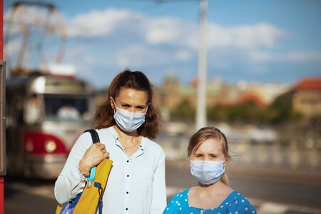 Life during coronavirus pandemic. modern mother and child with medical mask at tram stop outdoors in the city.