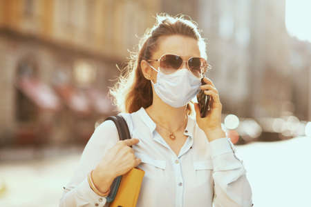 Life during covid-19 pandemic. stylish woman in blue blouse with medical mask, sunglasses and handbag using a smartphone outdoors on the city street. Banco de Imagens