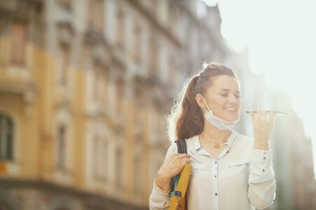 Life during coronavirus pandemic. smiling modern middle age woman in blue blouse with medical mask and handbag getting help from voice robot support outdoors in the city. or talking on a smartphone Stock fotó