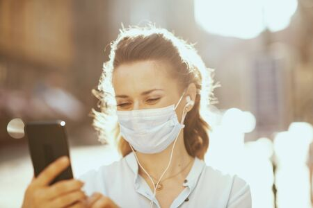Life during coronavirus pandemic. 40 years old woman in blue blouse with medical mask having virtual meeting outdoors on the city street.