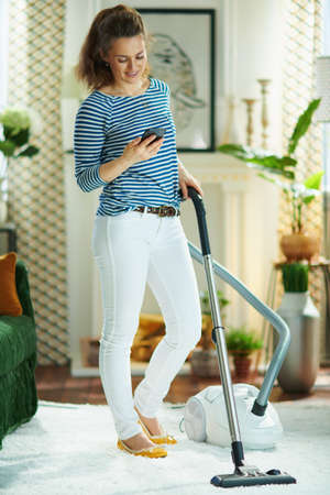 Full length portrait of happy modern female in striped t-shirt and white pants with vacuum cleaner using a smartphone at modern home in sunny day.