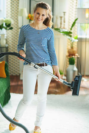smiling young housewife in striped t-shirt and white pants with vacuum cleaner in the modern living room in sunny day.