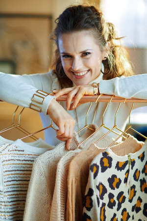 happy trendy 40 years old housewife in white sweater and skirt in the modern living room in sunny winter day choosing sweaters hanging on copper clothes rack. 免版税图像
