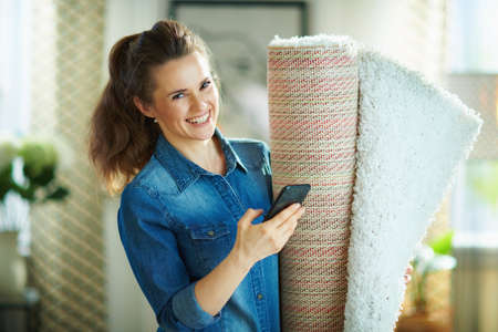happy young housewife in jeans shirt and white pants with white carpet in the modern living room in sunny day.