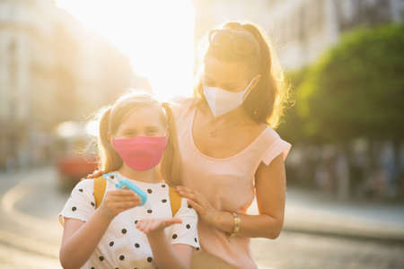 Portrait of elegant mother and child with masks and yellow backpack getting ready for school outside. Stock Photo