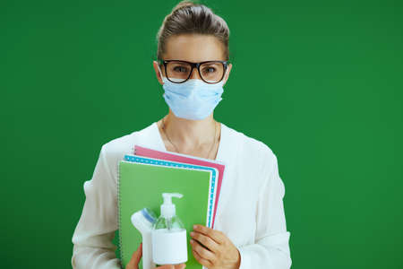 Portrait of modern woman pedagogue in white blouse with medical mask, digital thermometer and sanitizer against chalkboard green background.