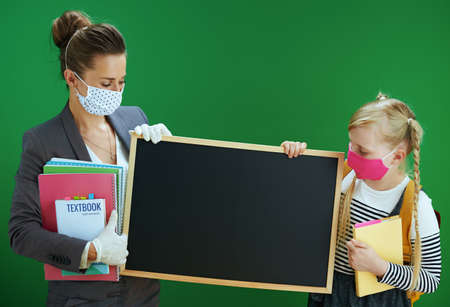 modern teacher woman and school girl with masks, yellow backpack and textbook measures temperature with digital thermometer isolated on chalkboard green.