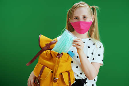 Life during coronavirus pandemic. modern school girl in white polka dot blouse with yellow backpack and pink mask pointing at copy space against chalkboard green background.