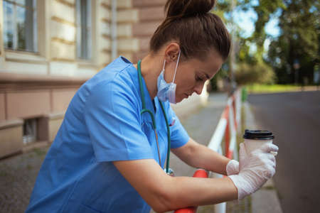 coronavirus pandemic. unhappy modern physician woman in scrubs with stethoscope and medical mask using a smartphone outdoors near clinic. Banco de Imagens
