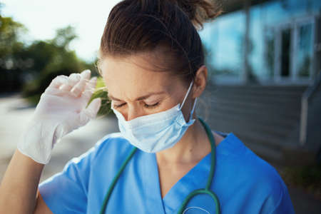 coronavirus pandemic. Closeup on medical doctor woman in scrubs with stethoscope and medical mask outdoors near hospital.