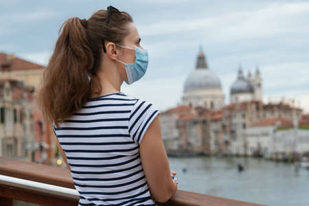 Travel during coronavirus pandemic. Seen from behind modern solo tourist woman with medical mask enjoying promenade on Accademia bridge in Venice, Italy. Banco de Imagens