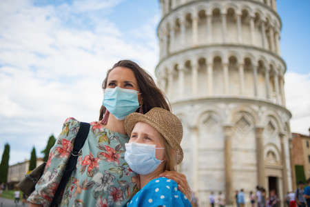 Travel during coronavirus pandemic. young mother and daughter tourists with medical masks enjoying promenade near leaning tower in Pisa, Italy.