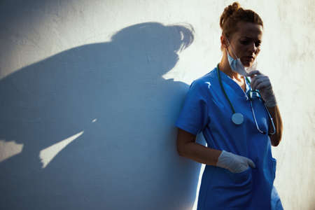 covid-19 pandemic. tired modern physician woman in scrubs with stethoscope, medical mask and rubber gloves outside near wall. Banco de Imagens