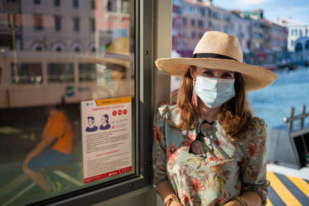 Venice - July, 25, 2020: modern tourist woman in floral dress with medical mask on vaporetto water bus stop in Venice, Italy.