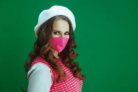 Life during coronavirus pandemic. Portrait of trendy learner woman in pink sleeveless shirt with pink medical mask isolated on green.
