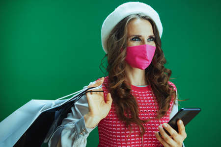 Life during covid-19 pandemic. Portrait of young woman shopper in pink sleeveless shirt with pink medical mask and shopping bags buying online on a smartphone isolated on green. Banco de Imagens