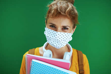 Life during coronavirus pandemic. Portrait of modern student woman in yellow shirt with medical mask, white headphones and backpack on green background.