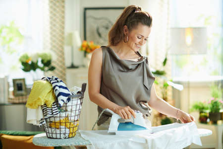Closeup on happy woman in silk blouse and beige pants with steam iron, ironing board, pile of folded ironed clothes and gold goblet at home in sunny day.