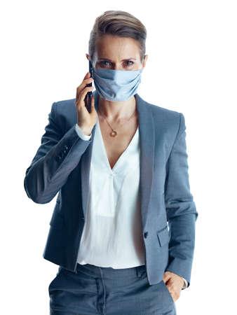 Business during covid-19 pandemic. Closeup on female in a grey suit with medical mask showing sanitiser isolated on white background. Stock Photo