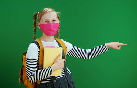 Life during covid-19 pandemic. modern child in white polka dot blouse with yellow backpack and pink mask dabbing against chalkboard green background.