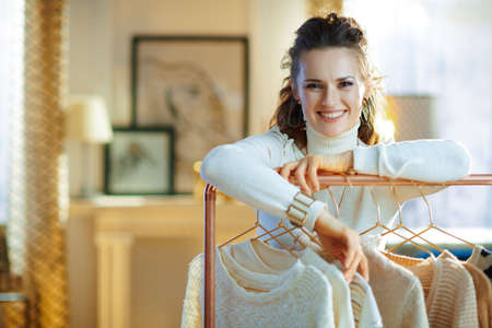 happy elegant woman in white sweater and skirt in the modern house in sunny winter day choosing sweaters hanging on copper clothes rack. Banco de Imagens