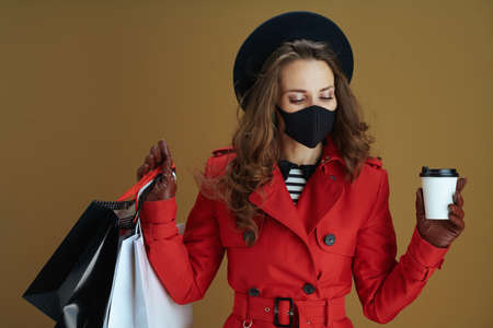 Hello autumn. modern 40 years old woman in red coat with black mask, shopping bags isolated on beige.