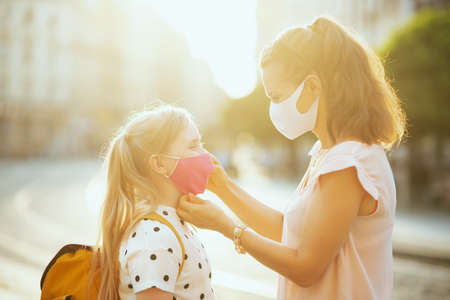 Life during covid-19 pandemic. young mother and child with masks and yellow backpack getting ready for school outside. Zdjęcie Seryjne