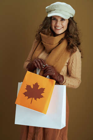 Hello october. smiling stylish 40 years old woman in scarf with leather gloves and paper shopping bag against beige background.