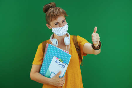 Life during covid-19 pandemic. smiling modern student woman in yellow shirt with medical mask looking up at copy space and listening to the music with headphones isolated on green background.