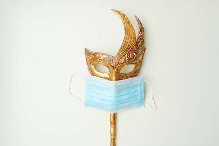 covid flat lay with venetian mask and medical mask on white background.