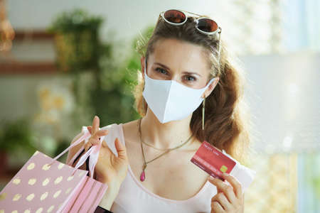 Life during covid-19 pandemic. Closeup on woman shopper with piggy bank, white rubber gloves and paper shopping bags. Banque d'images