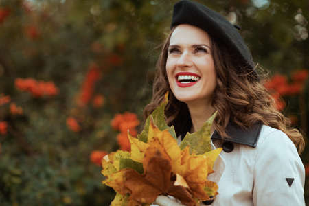Hello october. Portrait of smiling stylish female in beige trench coat outside on the city street in autumn. Stock Photo