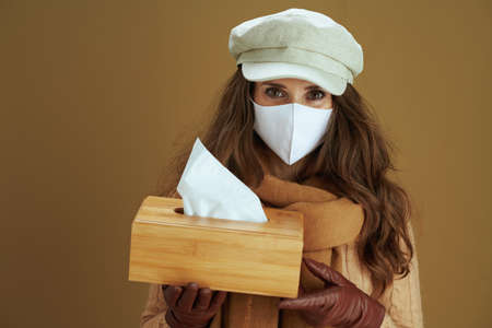 Life during coronavirus pandemic. elegant housewife in sweater with smartphone, white medical mask and credit card buying on internet isolated on beige background. Zdjęcie Seryjne