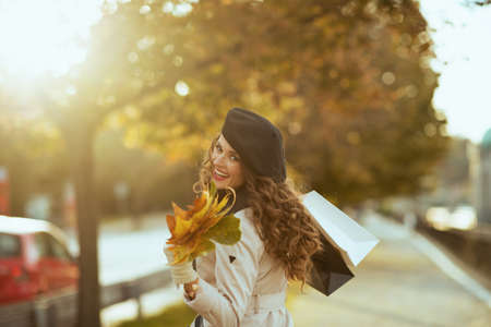 Hello november. happy modern middle aged woman in beige trench coat and black beret with shopping bags and autumn yellow leaves outdoors on the city street in autumn. Stock Photo