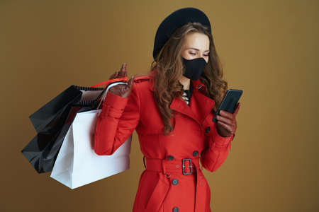 Life during coronavirus pandemic. stylish housewife in red coat with black mask, mug and paper shopping bags against bronze background.