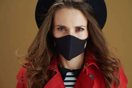 Life during coronavirus pandemic. stylish housewife in red coat with black mask, mug and paper shopping bags against bronze background. Stockfoto - 158046239