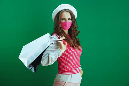 Life during coronavirus pandemic. Portrait of modern woman shopper in white beret with pink medical mask and shopping bags on green background.