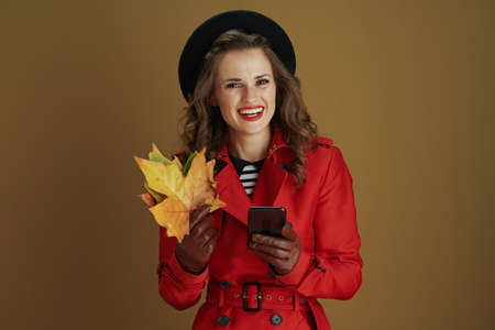 Hello october. smiling modern female in red coat and black beret with leather gloves showing blank board against bronze background.