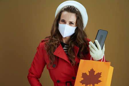 Life during coronavirus pandemic. Closeup on female in red coat showing smartphone blank screen isolated on beige.