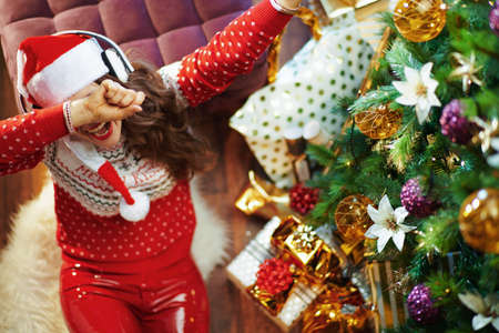 Merry Christmas. Upper view of stressed trendy middle aged housewife in gold sequin skirt and sweater near Christmas tree and gift boxes.