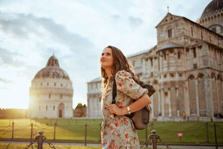 happy elegant middle aged traveller woman in floral dress with vintage camera and backpack near Cattedrale di Pisa.