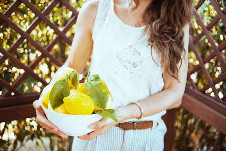 Closeup on woman in white shirt with plate of local farm lemons in the patio.