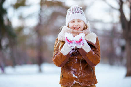 smiling stylish girl with mittens in a knitted hat and sheepskin coat playing outside in the city park in winter. 版權商用圖片 - 162896289