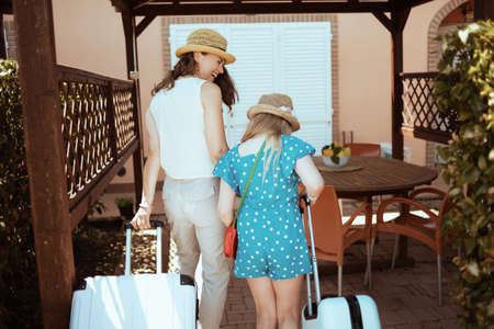Seen from behind trendy mother and daughter tourists in hats with trolley bags in the terrace of guest house hotel.