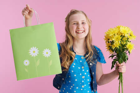happy stylish girl in dotted blue overall with yellow chrysanthemums flowers and green shopping bag isolated on pink background.