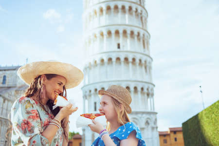 smiling stylish mother and daughter with pizza near Leaning Tower in Pisa, Italy.
