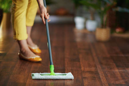 Closeup on woman with mop doing housekeeping at home in sunny day.